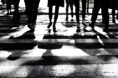 Oskarpa skuggor och konturer av folk på tvärgata fotografering för bildbyråer
