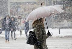 Oskarpa unga kvinnor som går under paraplyet i tungt snöfall royaltyfria bilder