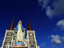 Oskuld Mary Statue med bakgrund för kyrklig och blå himmel royaltyfri foto