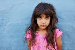 Oskyldigt liten flickaanseende mot den blåa väggen Royaltyfri Bild