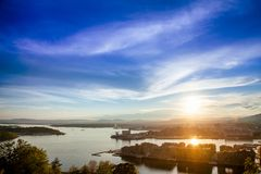 Oslo cityscape at sunset Norway Scandinavia. Oslo cityscape as viewed from the Ekeberg hill at sunset with sun reflecting in Oslofjord, Norway, Scandinavia royalty free stock image