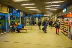 OSLO NORGE - MARS, 26, 2018: Turister crrosing under den informativa skärmen av avvikelser ankomster på den Oslo centralen arkivfoto