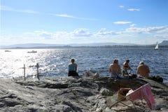Oslo, Noruega - 24 de julio de 2018: Tomar el sol a gente en costa rocosa en el fiordo de Oslo imagen de archivo libre de regalías