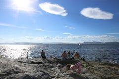 Oslo, Noruega - 24 de julio de 2018: Tomar el sol a gente en costa rocosa en el fiordo de Oslo imagen de archivo