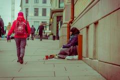 OSLO, NORUEGA - MARZO, 26, 2018: Opinión al aire libre la gente no identificada que camina cerca de un hombre sin hogar que se si imagen de archivo libre de regalías