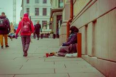 OSLO, NORUEGA - MARZO, 26, 2018: Opinión al aire libre la gente no identificada que camina cerca de un hombre sin hogar que se si fotos de archivo libres de regalías