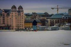 OSLO, NORVEGIA - 26 MARZO, 2018: Il bello punto di vista all'aperto della donna non identificata con lo skii copre all'edificio d Fotografie Stock