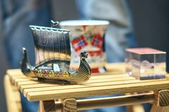 Metal Viking toy ship also known as karve or knarr and traditional Norwegian mug with National flag at the display stock images