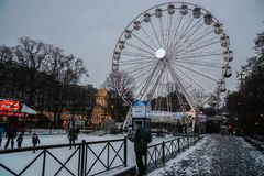 Oslo / Norway - December 05 2018: Old man look at children with ice skate in Christmas carnival with ferris wheel royalty free stock photography