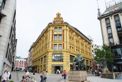 Oslo, Norway - February 02, 2010: statue of Christian Krohg at Karl Johans gate. Shopping mall building on pedestrian. Street in downtown. Shopping destination Royalty Free Stock Images