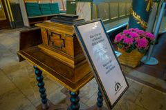 OSLO, NORWAY - MARCH, 26, 2018: Interior view of informatie sign of asking for contribution in a wooden box at the Oslo. `s Cathedral, in Norway Royalty Free Stock Image