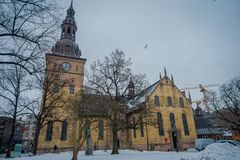 OSLO, NORWAY - MARCH, 26, 2018: Outdoor view of Domkirke Cathedral in Oslo with some dry trees in front at Oslo. Norway stock photography