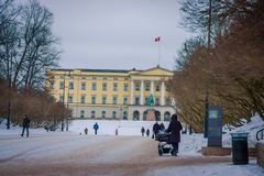 OSLO, NORWAY - MARCH, 26, 2018: Outdoor view of unidentified people walking in front of the Royal Palace, was built in. The first half of the 19th century in Stock Photography