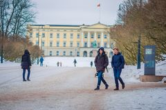 OSLO, NORWAY - MARCH, 26, 2018: Outdoor view of unidentified people walking in front of the Royal Palace, was built in. The first half of the 19th century in Stock Image