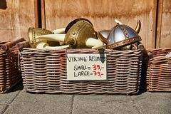 Toy horned helmets in traditional Norwegian style in wicker basket are sold on the street in front of a souvenir gift royalty free stock photography