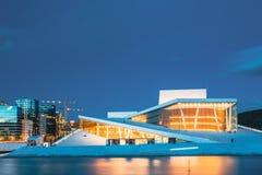 Oslo Norwegen Gl?ttung von Ansicht des belichteten Opern-Ballett-Hauses unter hohen Geb?uden unter blauem Himmel stockfotos