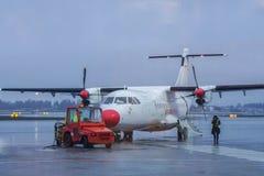Oslo/Norwegen - 30. November 2018: Wideroe-Propellerflugzeug an der Rollbahn mit Fracht-LKW für die Abreise zu Lofoten-Inseln stockbild