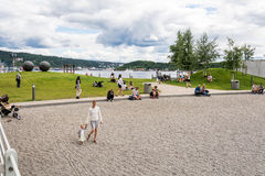 Oslo people on harbour beach Aker Brygge Royalty Free Stock Image
