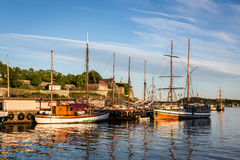 Oslo port and Akershus Fortress. Sunset over the Oslo harbor with many old wooden sail boats and the Akershus Fortress in the background in Norway capital city royalty free stock photos