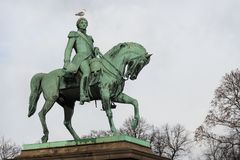 Oslo royal palace monument of king karl johan with bird on head, view from parkway alley boulevard avenue with autumn leaves, nor stock photography