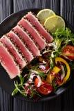 Osmalony ahi tuńczyk pokrywał sezamowych ziarna z sałatką na czarnego talerza cl Obraz Stock
