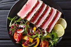 Osmalony ahi tuńczyk pokrywał sezamowych ziarna z sałatką na czarnego talerza cl Zdjęcie Royalty Free