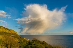 Osmington Bay, Jurassic Coast, Dorset, UK. Single Raincloud with a little bit of a rainbow at Osmington Bay, near Weymouth, Jurassic Coast, Dorset, UK Royalty Free Stock Photography