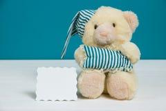 Oso beige lindo con un gorro de dormir, una almohada y una tarjeta en el fondo blanco, azul Foco selectivo, efecto de la película Imagen de archivo libre de regalías