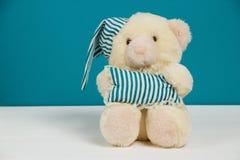 Oso beige lindo con un gorro de dormir y almohada en el fondo blanco, azul Foco selectivo, entonado, efecto de la película, copia Foto de archivo libre de regalías