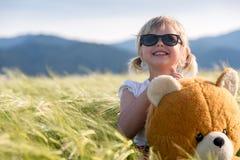 Oso de la muchacha y de peluche en un campo de trigo Imagen de archivo