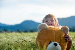 Oso de la muchacha y de peluche en un campo de trigo Imágenes de archivo libres de regalías