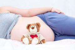 Oso de peluche al lado del vientre de una mujer embarazada Fotografía de archivo