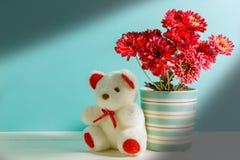 oso de peluche blanco hermoso, flor rosada en florero en el wo blanco, verde Imagen de archivo libre de regalías