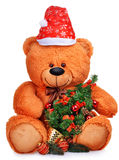 Oso de peluche clásico en sombrero rojo con el árbol de navidad Foto de archivo