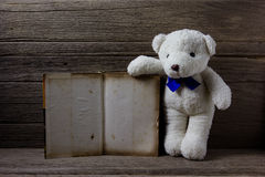 Oso de peluche con el libro viejo en el fondo de madera, aún vida Imágenes de archivo libres de regalías