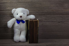 Oso de peluche con el libro viejo en el fondo de madera, aún vida Fotos de archivo