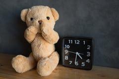 Oso de peluche con el reloj, oso de peluche que se sienta en piso de madera contra fotos de archivo