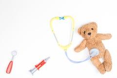 Oso de peluche con las herramientas de la medicina del estetoscopio del juguete y del juguete en un fondo blanco Fotografía de archivo
