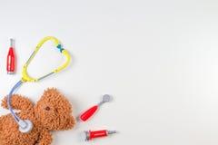 Oso de peluche con las herramientas de la medicina del estetoscopio del juguete y del juguete en un fondo blanco Visión superior Fotografía de archivo