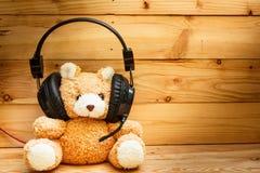Oso de peluche con los auriculares Imágenes de archivo libres de regalías