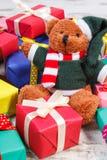 Oso de peluche con los regalos coloridos para la Navidad o la otra celebración Imagenes de archivo