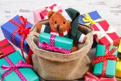 Oso de peluche con los regalos coloridos para la Navidad o la otra celebración Imagen de archivo
