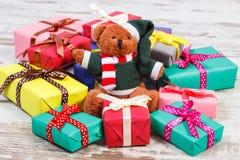 Oso de peluche con los regalos coloridos para la Navidad o la otra celebración Foto de archivo