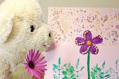 Oso de peluche con una flor púrpura que mira una pintura Foto de archivo
