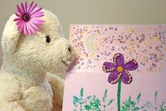 Oso de peluche con una flor púrpura que mira una pintura Fotografía de archivo