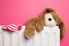 Oso de peluche de Childs y manoplas en un radiador del dormitorio Fotos de archivo