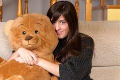 Oso de peluche del abarcamiento de la mujer joven que se sienta en el sofá Foto de archivo libre de regalías