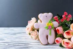 Oso de peluche delicioso de la galleta del pan de jengibre con las flores en un de madera Fotografía de archivo libre de regalías
