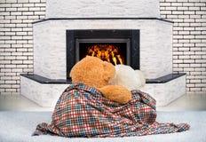 Oso de peluche dos que abraza y que mira fijamente la llama del fuego en la chimenea Foto de archivo