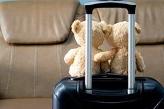 Oso de peluche dos que se sienta en un equipaje en alojamientos Turista a imagenes de archivo